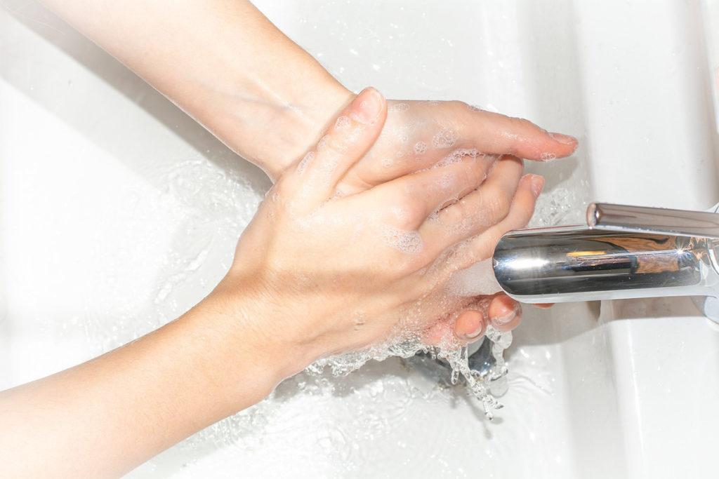Homme blanc se lavant les mains après avoir épluché des courgettes
